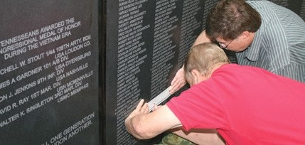 James Dean, left, assisted Ricky Brown in etching his uncle's name from the Tennessee Vietnam Veterans Memorial Wall displayed in Cleveland, TN. PHOTO BY Joyanna Love, The Cleveland Daily Banner