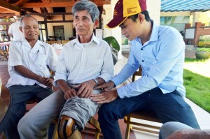 Nguyen Tien,    center,    a former Viet Cong soldier,    shows U.S. Marine veterans his wooden leg while having coffee at the Red Beach Resort in Da Nang,    Vietnam,    on Sept. 25,    2015. At left is Phan Van Tai,    a former Viet Cong captain. (Erik Slavin/Stars and Stripes)